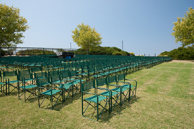 Green chairs in an improvised outdoor concert venue