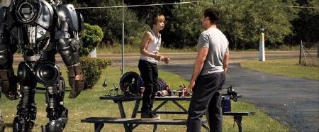 Dakota Goyo shows Hugh Jackman Atoms functions from the Walt Disney Studios film Real Steel