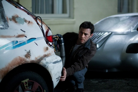 Joe hides behind a car from the Endgame Entertainment film Looper