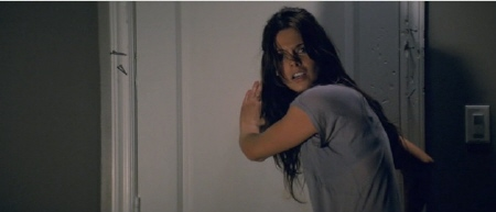 Ashley Green tries to nail a door shut from the Dark Castle Entertainment film The Apparition